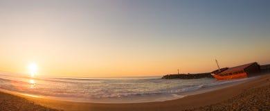 Coucher du soleil de paysage marin avec le naufrage sur la plage Images stock
