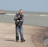 Coucher du soleil de pelliculage d'homme d'appareil-photo au-dessus de la mer Image stock