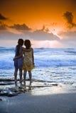 Coucher du soleil de plage de filles Photographie stock