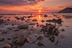 Coucher du soleil de plage rocheuse Photo stock