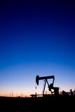 Coucher du soleil de pumpjack de puits de pétrole Image stock