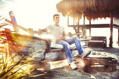 Coucher du soleil de sérénité et de paix avec l'homme s'asseyant sur le bateau Images libres de droits