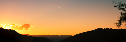 Coucher du soleil de silhouette au-dessus des montagnes Photo stock