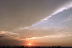 Coucher du soleil de soirée avec les cieux nuageux et la scène de bâtiment de silhouette Photos libres de droits
