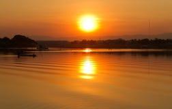 Coucher du soleil de village de rivière. Photo stock