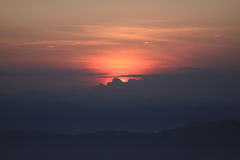 Coucher du soleil derrière des nuages Photos stock