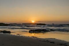 Coucher du soleil derrière des vagues Photos stock
