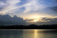 Coucher du soleil derrière le lac et la colline à la tombée de la nuit Photos stock