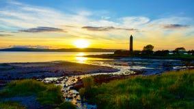 Coucher du soleil derrière le monument de crayon dans Largs Image stock