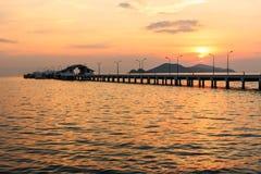 Coucher du soleil derrière le petits bateau de port et courrier de lampe Photographie stock