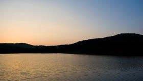 Coucher du soleil derrière les montagnes Photos stock