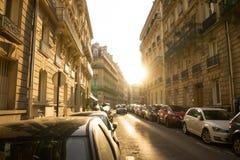 Coucher du soleil derrière un bâtiment sur une rue parisienne Images stock