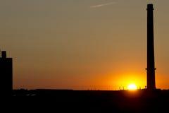 Coucher du soleil derrière une cheminée d'usine Images libres de droits