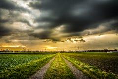 Coucher du soleil dramatique de ciel de route de campagne photos stock