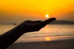 Coucher du soleil en main Photo stock