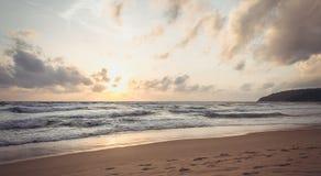 Coucher du soleil en mer, plage isolée, nuages couvrant partiellement le soleil Images libres de droits