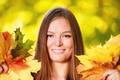 Coucher du soleil en parc Femme de fille de portrait tenant les feuilles automnales en parc Photo libre de droits