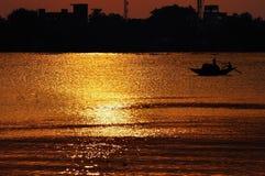 Coucher du soleil, entête de bateau de pays vers les rayons d'or Image stock