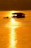 Coucher du soleil et bateau avec la maison de flottement Photographie stock