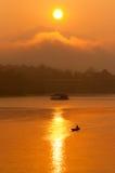 Coucher du soleil et bateau avec la maison de flottement Photographie stock libre de droits