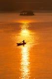 Coucher du soleil et bateau avec la maison de flottement Photo stock