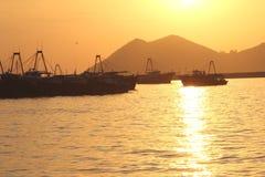 Coucher du soleil et bateaux de pêche à l'île de Cheung Chau photographie stock libre de droits
