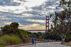 Coucher du soleil et cyclistes de golden gate bridge sur Marin County Road photographie stock
