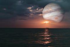 coucher du soleil et Jupiter sur le clou coloré de mer de surface horizontale d'eau photo stock