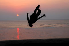 Coucher du soleil et silhouette d'un danseur dans la plage Image stock