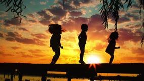 Coucher du soleil et silhouettes des enfants heureux sautant sur le pilier en bois au-dessus de l'eau de lac banque de vidéos