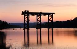 Coucher du soleil et silhouettes sur la rivière Photographie stock libre de droits