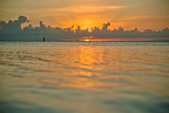 Coucher du soleil et siluet de pêcheur très loin photo libre de droits