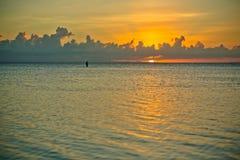 Coucher du soleil et siluet de pêcheur très loin photographie stock