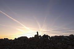 Coucher du soleil et traces de fond et d'avion de ciel bleu Photo libre de droits