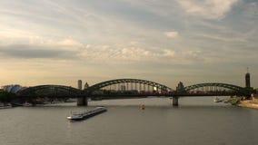 Coucher du soleil et trains sur le pont de Hohenzollern avec des pétroliers naviguant sur la rivière le Rhin, Allemagne banque de vidéos
