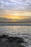 Coucher du soleil et vagues molles à la plage beal Images stock