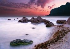 Coucher du soleil excessif de mer avec les montagnes silhouettées Photographie stock
