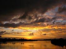 Coucher du soleil excessif et nuages au-dessus de fleuve photos stock