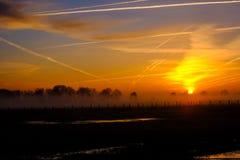 Coucher du soleil flou coloré dans les domaines avec le ciel nuageux Photographie stock libre de droits