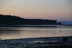 Coucher du soleil glorieux mais gelant au-dessus d'une baie côtière écossaise de village Photo libre de droits