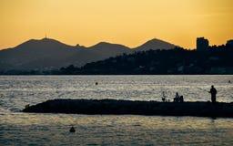 Coucher du soleil jaune lumineux sur la plage avec le coucher du soleil dans des goupilles de les de Juan, ` Azur, France de Cote Photo stock