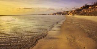 Coucher du soleil jaune sur la plage, avec petites collines Photographie stock libre de droits