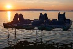 Coucher du soleil du Lac Balaton avec des bateaux de pédale dans l'avant Photos stock