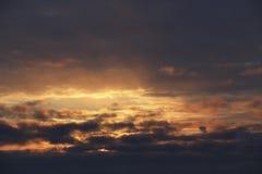 Coucher du soleil le ciel d'hiver de soirée en nuages foncés denses le soleil brille la lumière chaude jaune lumineuse par l'air  Image stock
