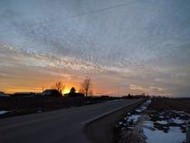 Coucher du soleil le long de route de campagne Photographie stock libre de droits