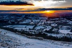 Coucher du soleil neigeux d'hiver au-dessus du Cotswolds, R-U Moutons se blottissant pour la chaleur photographie stock