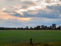 Coucher du soleil nuageux au-dessus de champ rural de ferme Image stock