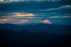 Coucher du soleil nuageux au-dessus des montagnes Photo libre de droits