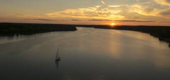 Coucher du soleil nuageux coloré avec le yacht Photographie stock libre de droits