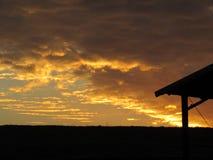 Coucher du soleil nuageux d'or avec le paysage rural Photos stock